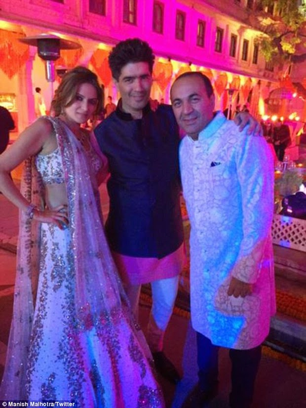 On the Left Bride in lehenga saree and right side Groom in white sherwani with Manish Malhotra
