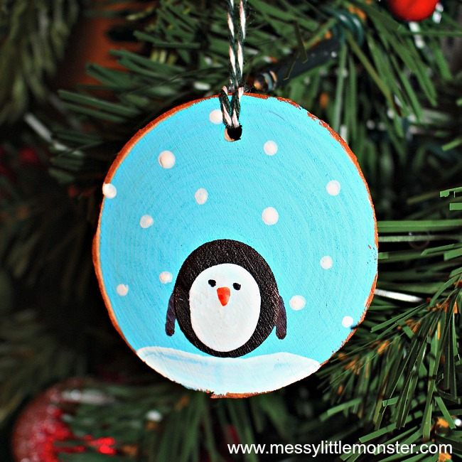 How to make fingerprint penguin wood slice Christmas ornaments. An easy kid - made Christmas ornament DIY for toddlers and preschoolers that doubles up as a keepsake. Great for a penguin, snow or winter project.