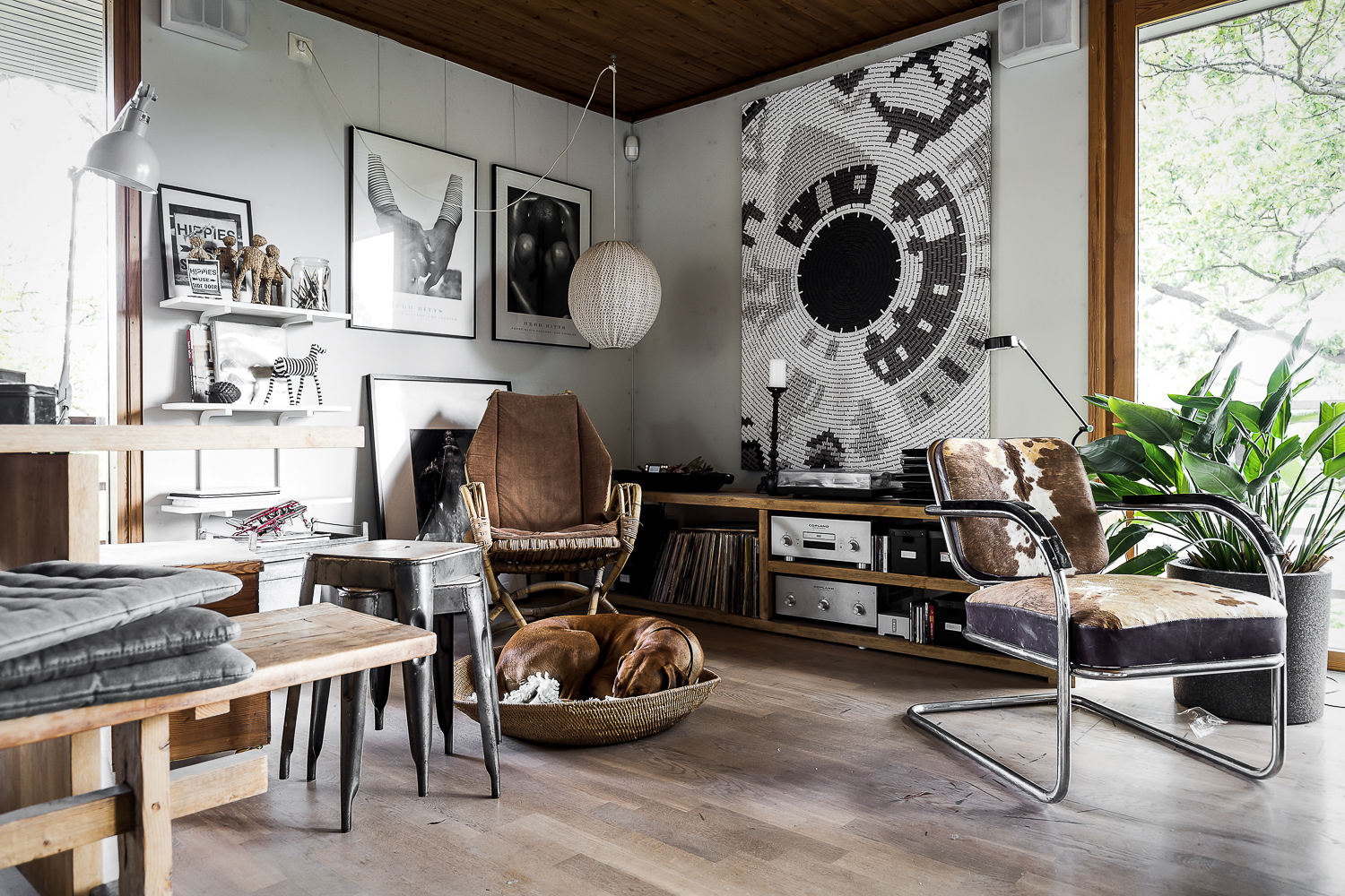 Scandinavian villa with oriental and rustic decor containing tolix chairs, Arne jacobsen lamp, cowhide chair and wood