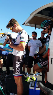 Peter Sagan is signing autographs while Daniel Oss looks on from the team van.  Peter Sagan is writing on a blue Tour Down Under souvenir hat.