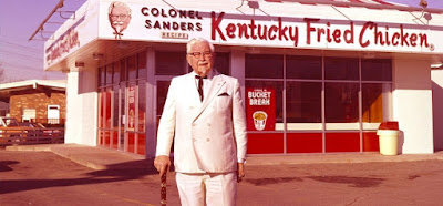 Colonel Sanders standing in front of KFC restaurant