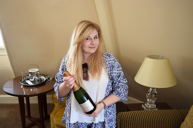 Grace is holding a bottle of Champagne
