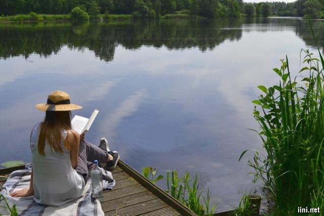 ảnh cô gái đọc sách bên hồ nước