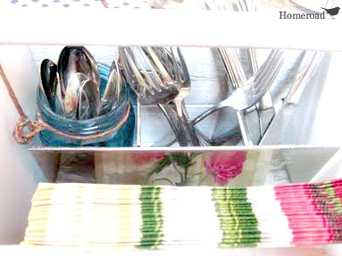 crate filled with silverware, mason jars and napkins