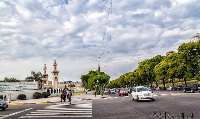 Paisaje con nubes, gente y tránsito automotor.