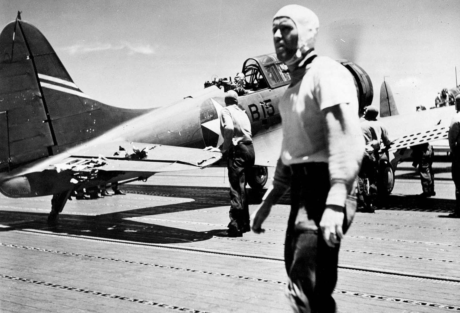 An SBD-3 dive bomber of Bombing Squadron Six, on the deck of USS Yorktown. The aircraft was flown by Ensign G.H. Goldsmith and ARM3c J. W. Patterson, Jr., during the June 4, 1942 strike against the Japanese carrier Akagi. Note the battle damage on the tail.