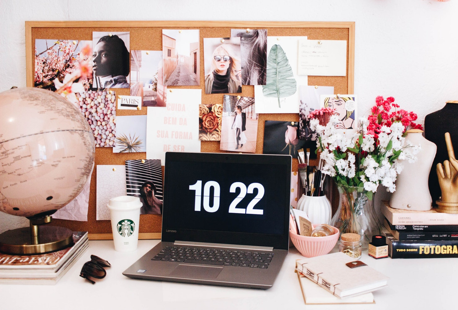 desk of a small business owner with a laptop and notice board