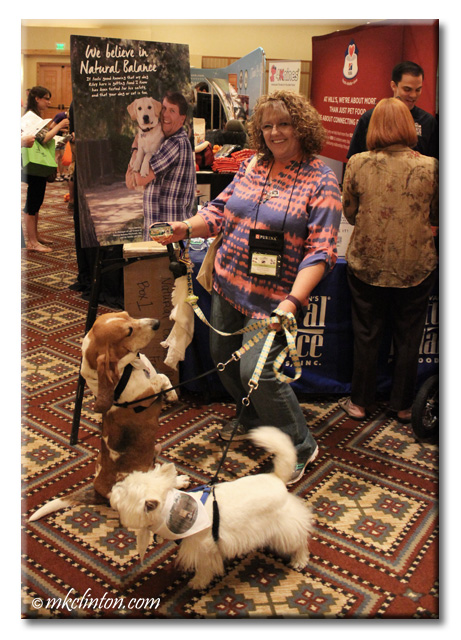 M. K. Clinton posing in front of Natural Balance display with Bentley Basset & Pierre Westie