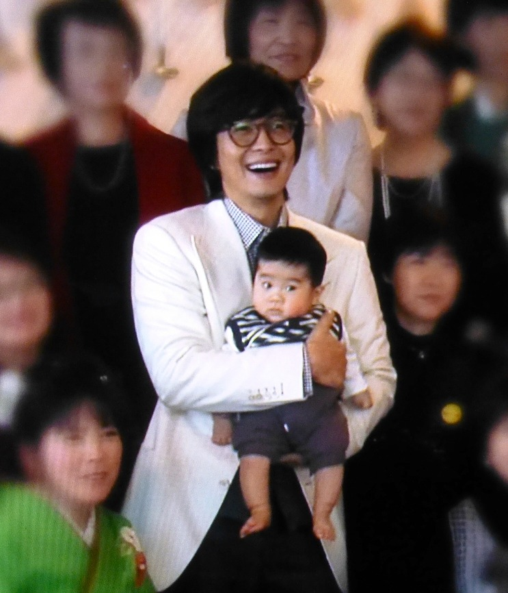 Bae Yong-Joon holding his first child, a son born on October 23, 2016
