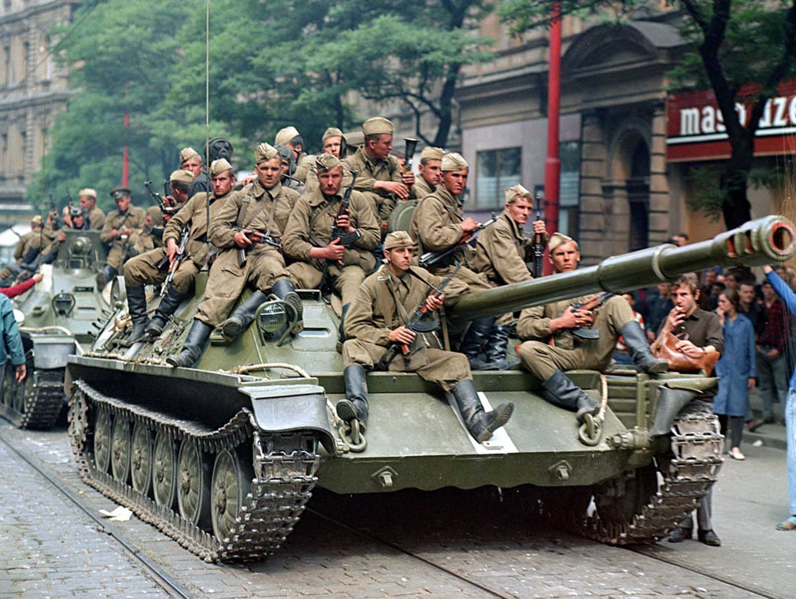 Soviet army soldiers sit on their tanks in front of the Czechoslovak Radio building, in central Prague, on August 21, 1968.
