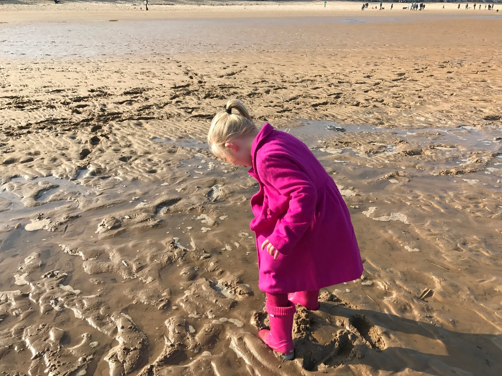 A 5 year old girl all dressed in pink looks down at her pink wellies as her feet sink in wet sand