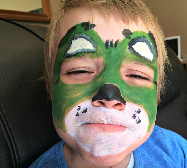 a little boy with face paints to make him look like a bear