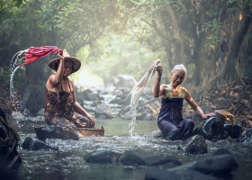Women washing clothes at the river.