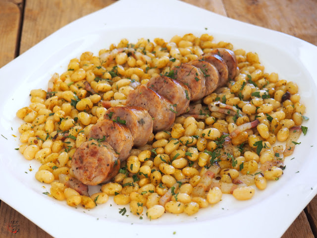 Judías secas cocidas y salteadas con ajo, perejil  y panceta, que acompañan a una butifarra a la plancha