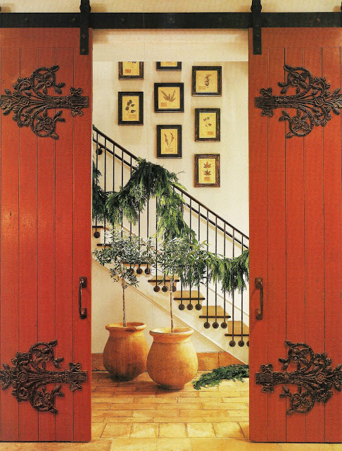 Pamela Pierce Designed home with garland on staircase and sliding antique barn doors