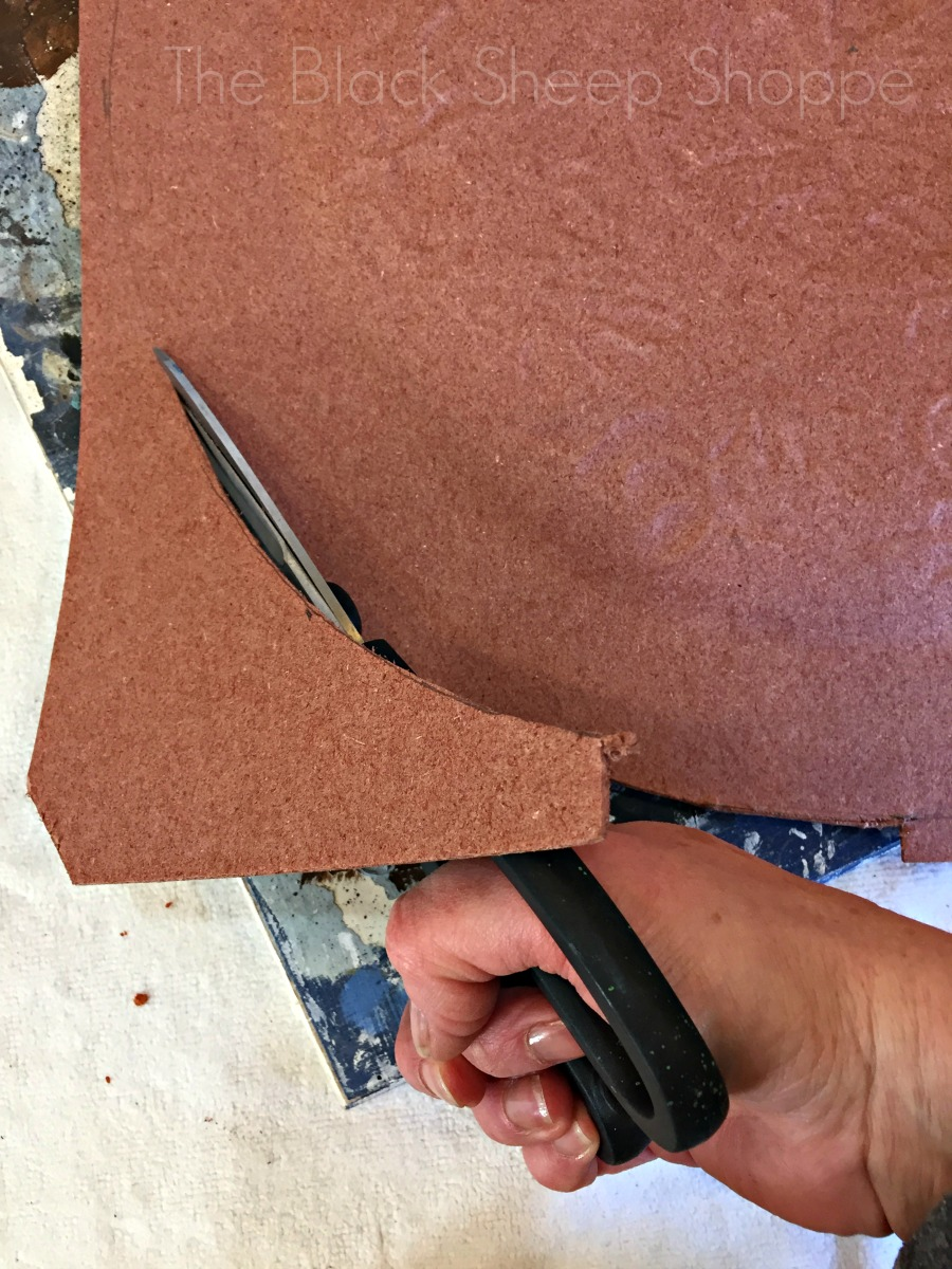 Cutting through fiberboard with scissors