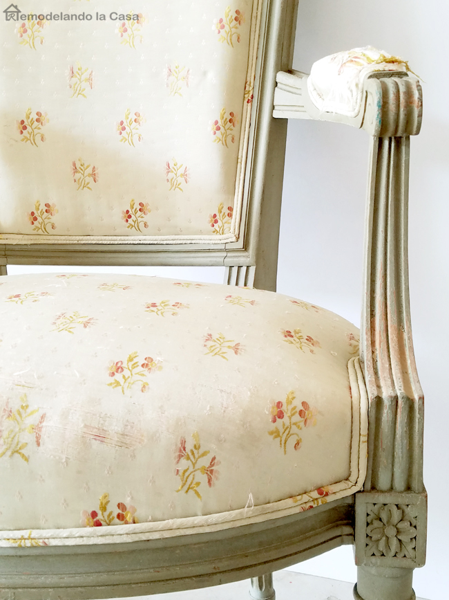 old chair with wooden details, rosettes in legs, green upholstered fabric with little red flowers