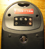[Image: Backside of the GPS receiver showing a six-pin connector and a Dymo label 'WINDYTAN'.]