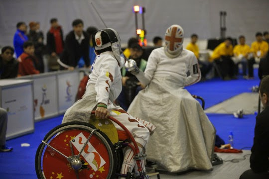 Photo of two wheelchair users fencing