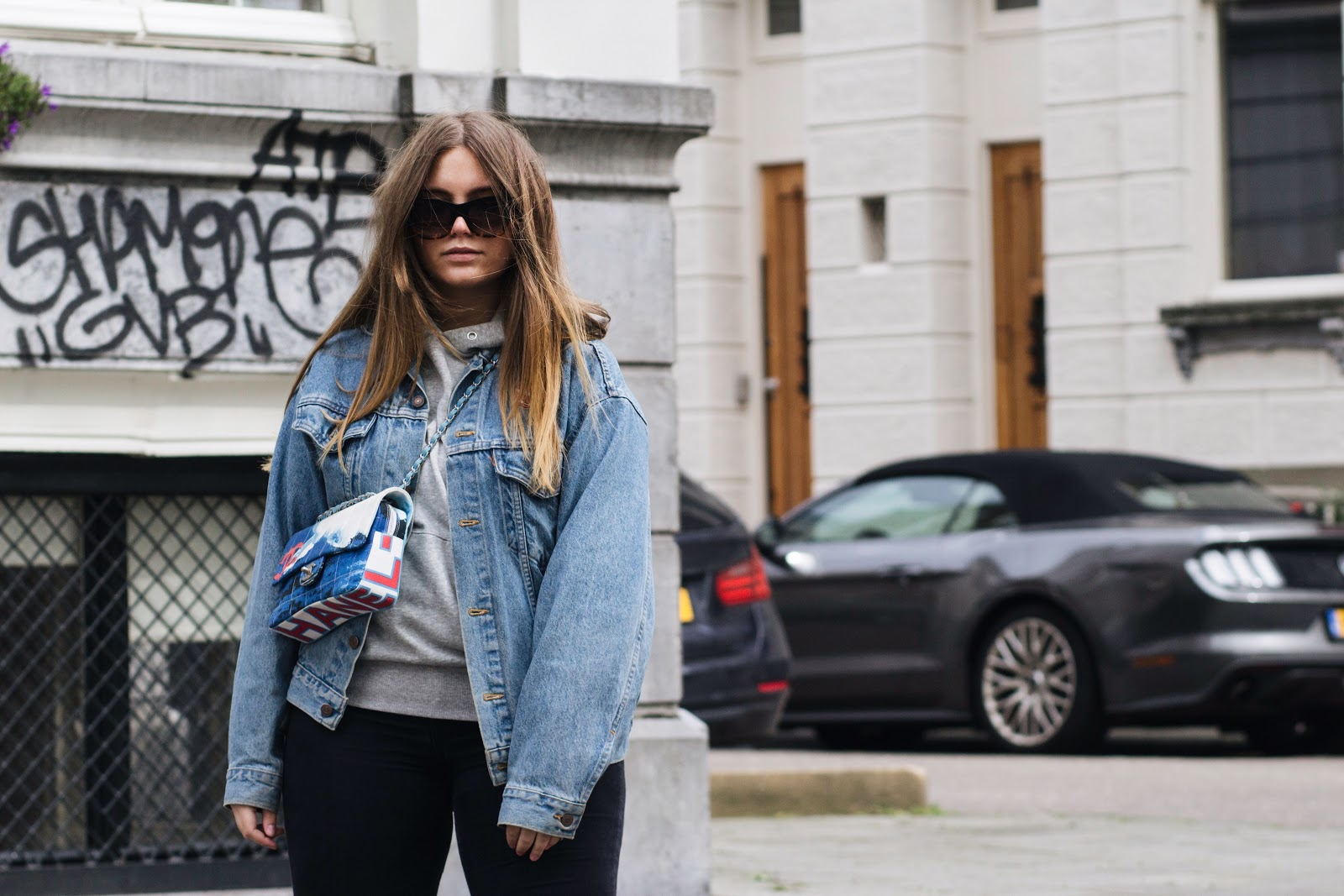 fashion blogger dominique candido wearing a levi's jacket with a h&m hoodie, gucci snake loafers, black asos jeans, celine sunglasses and a chanel bag