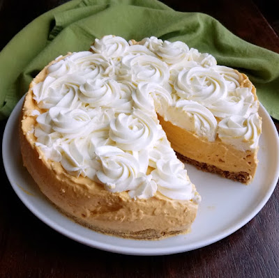 pumpkin no bake cheesecake with swirls of cream cheese whipped cream on top