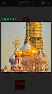 Церковь с позолоченными куполами, один из которых покрыт строительными лесами
