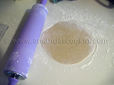 A photo of a rolled out flour tortilla with a purple rolling pin to the side.