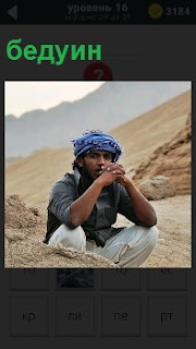 Кочевник сидит в пустыне, который ведет кочевой образ жизни как бедуин