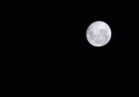 Imagen de una luna llena solitaria escorada a la derecha en un gran cielo negro