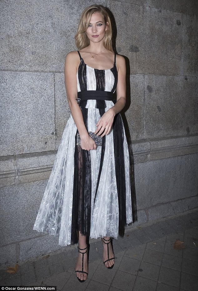 Karlie Kloss dazzled in a black and white striped dress as she jetted to Madrid,Spain on Monday to celebrate designer Carolina Herrera's 35 year fashion career