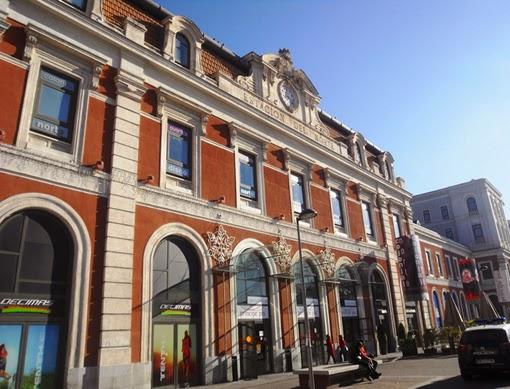 Fachada ocre y blanca de un edificio clasico de tres plantas en el que destacan los arcos de la planta baja.