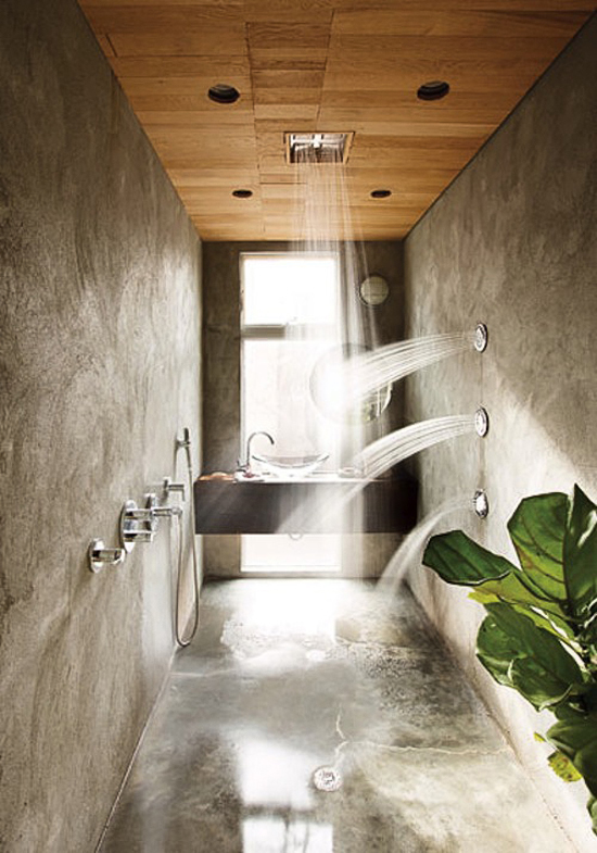 Stucco shower with numerous showerheads and wooden ceiling designed by Hank Mitchell via New York Magazine.