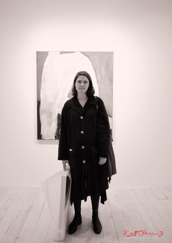 Lottie Consalvo at Gallery 9  with her painting in the background, New Strokes exhibition.