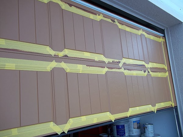 tape off panels on a garage door being painted to look like wood