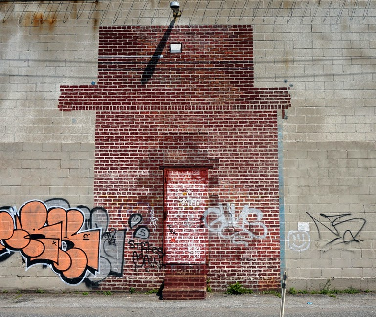 Mural of red brick wall painted on gray cinder block wall
