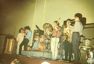 The Electric Flag onstage at the Fillmore Auditorium, August 29, 1967. From left, Barry Goldberg (hidden), Nick Gravenites, Michael Bloomfield, Buddy Miles (behind drums), Harvey Brooks, unknown and Peter Strazza.