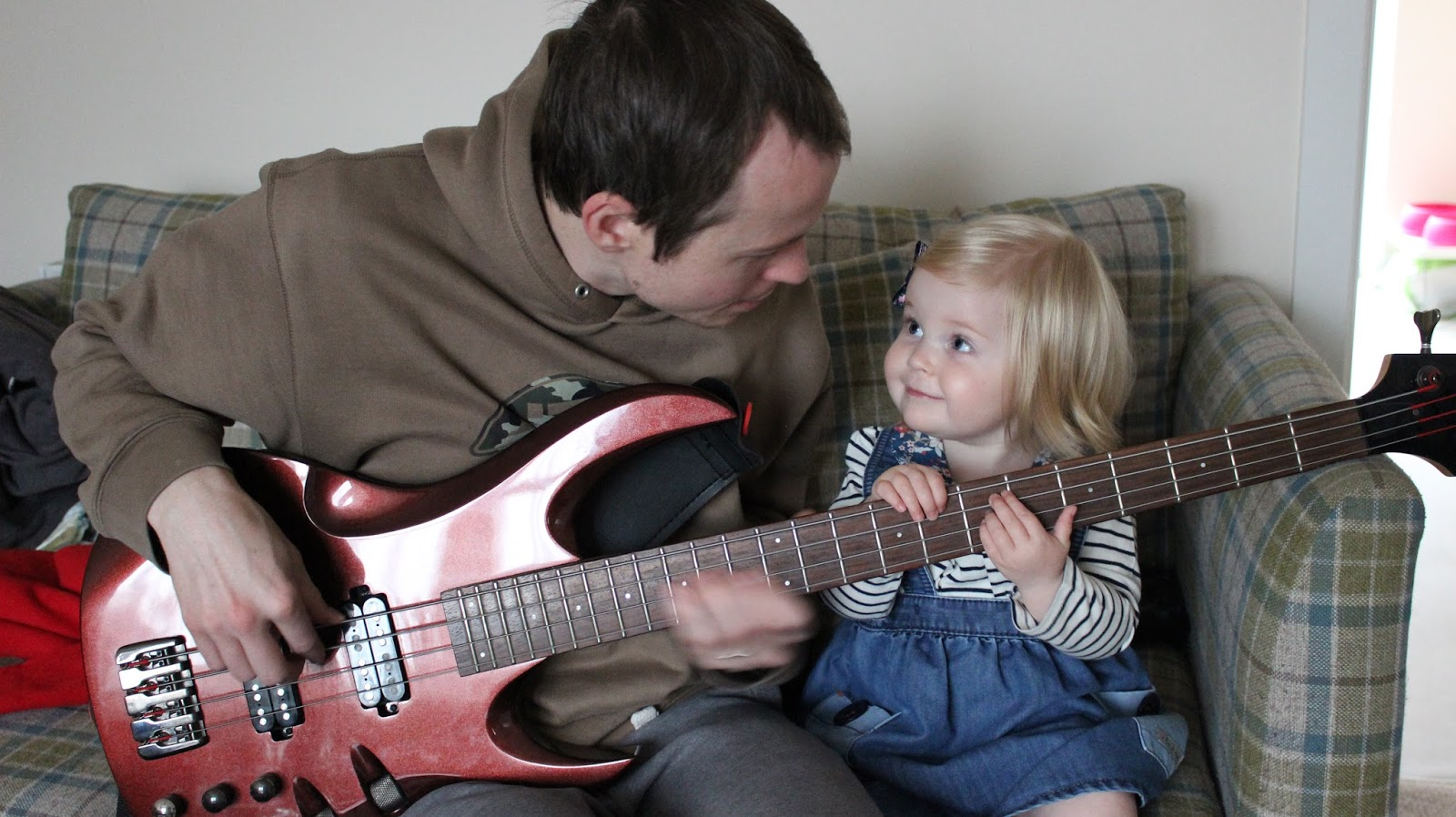 my husband sat on the sofa with my two year old. They are both holding onto my husbands burgundy coloured bass guitar and smiling at each other.