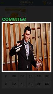 мужчина сомелье за работой, наливает вино в длинный графин
