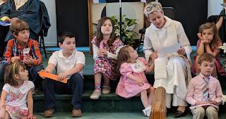 children sit on steps clustered around Pastor Jenny