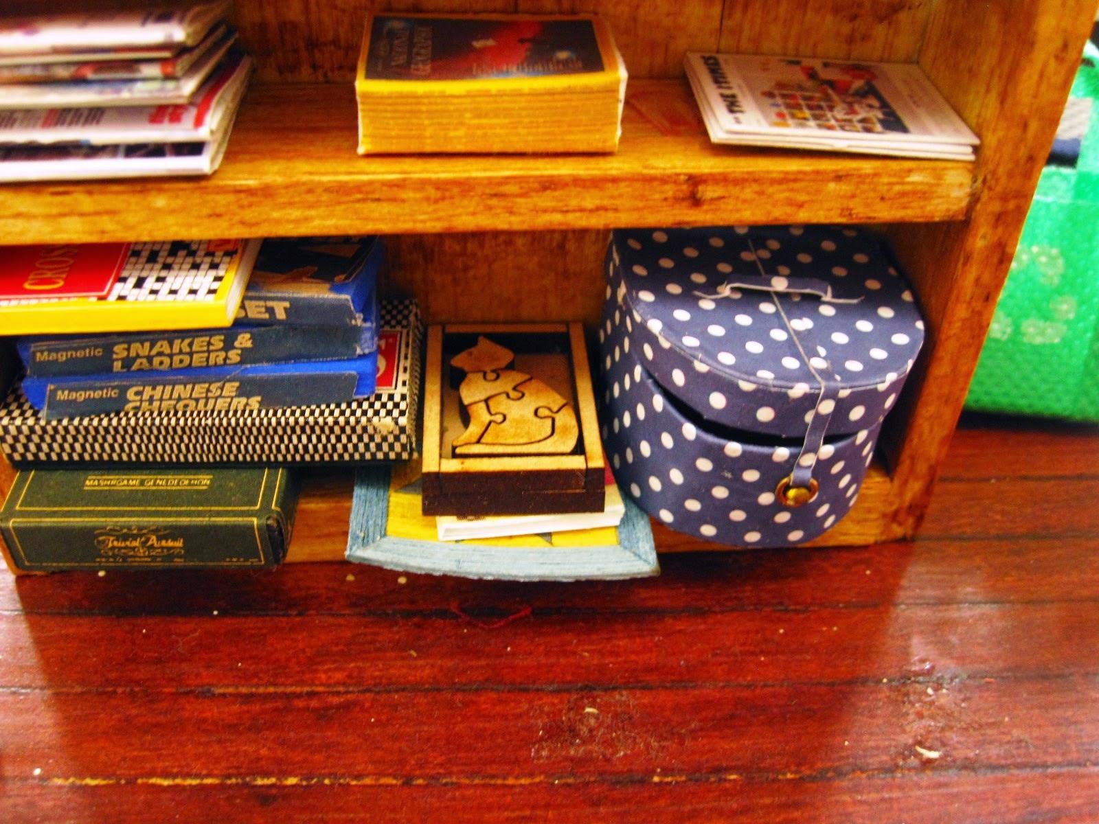 Modern dolls' house miniature games shelf.