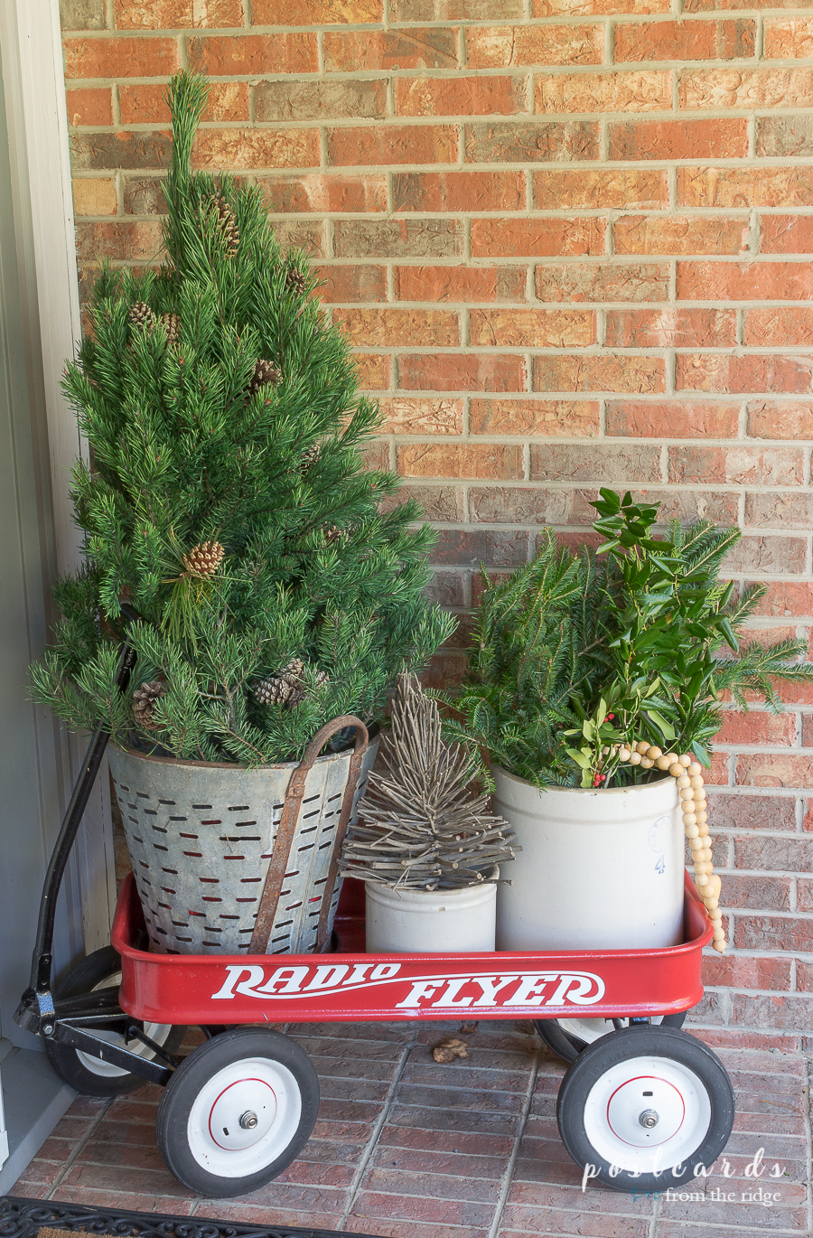 red radio flyer wagon with small Christmas tree and vintage stoneware crock