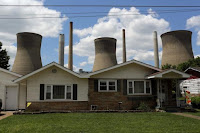 The John Amos coal-fired power plant is seen behind a home in Poca, West Virginia in this May 18, 2014 file photo. (Credit: Reuters/Robert Galbraith/Files)  Click to Enlarge.