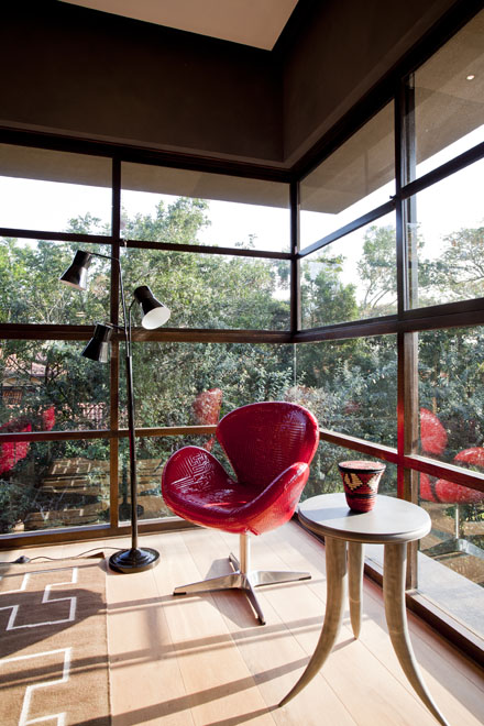 One of the rooms with red chair and big windows in Contemporary South African SGNW House by Metropole Architects