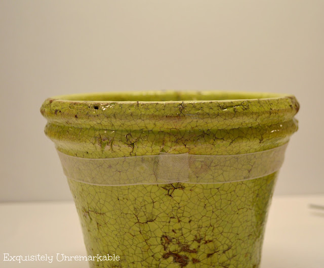 Green flower pot with white ribbon around top