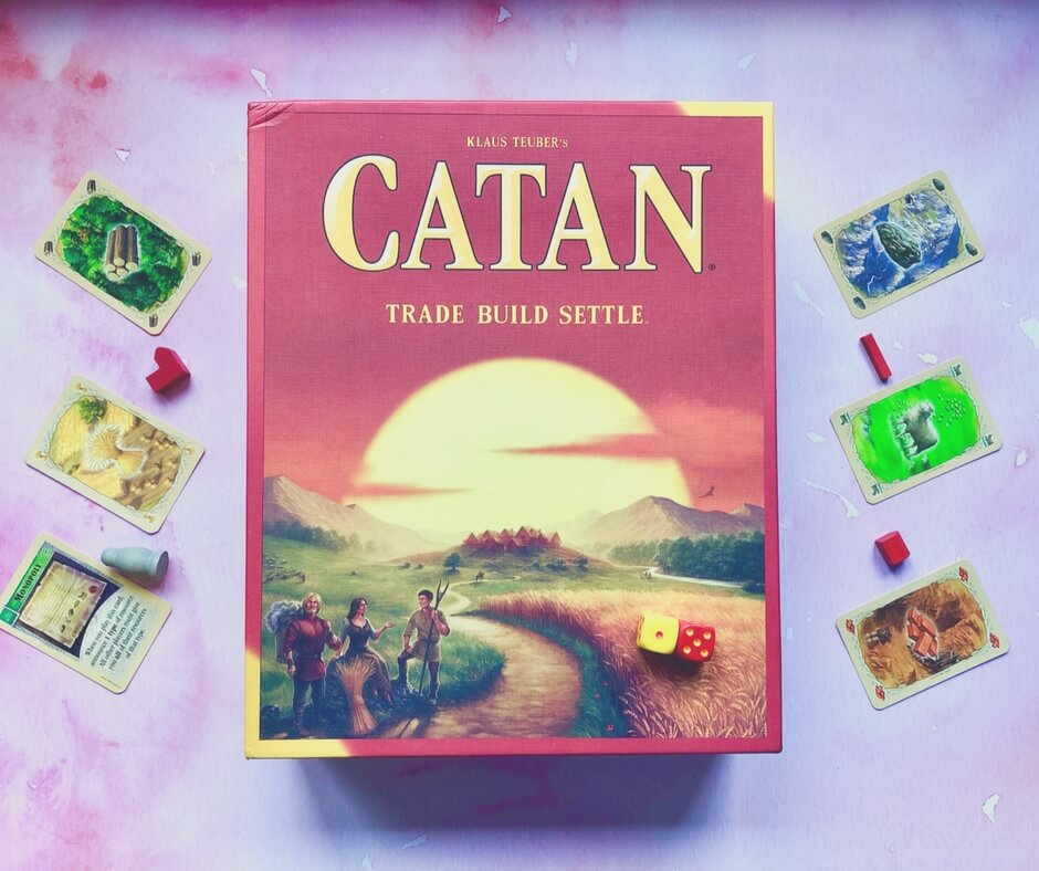 "The board game Catan sits in the middle of the frame with 3 cards either side of it. The cards each have a different picture; wood, hay,  rock, sheep, brick, and a ""monopoly"" card. There's a pink background."