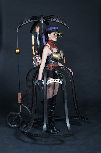 Steampunk women's costume art piece: steel cage skirt with penny-farthing wheel, steel parasol, steam powered backpack and steam gauge bra, boots, goggles and hat.
