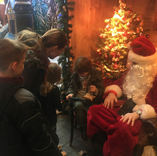 Autistic boy with iphone and rest of family with Santa