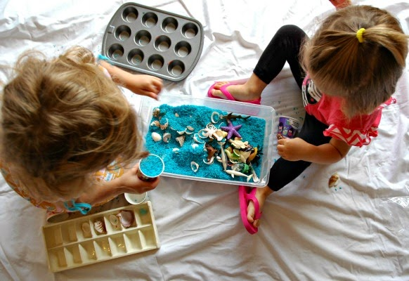 blue rice ocean sensory bin, shot from above, girls playing
