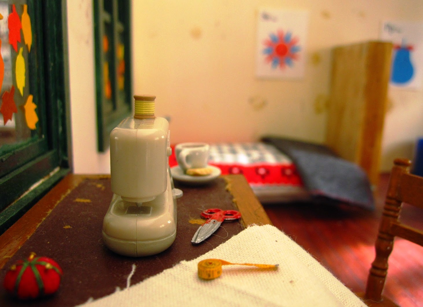 Miniature holiday home interior with a sewing machine, fabric, tape measure, pin cushion and scissors on an old desk.