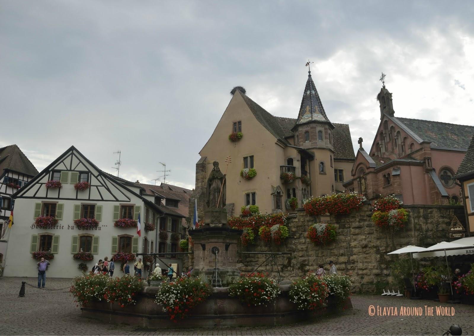Plaza principal de Eguisheim con la fuente renacentista y la iglesia de san Pedro y san Pablo en Eguisheim